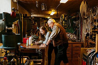 Rope maker and his teenage apprentice looking at cell phone - p352m2041148 by Folio Images