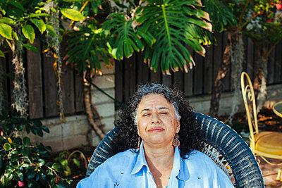 Hispanic woman relaxing in backyard - p555m1408767 by Shestock