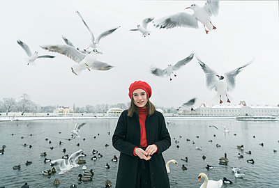 Young woman feeding seagulls - p1437m1584894 by Achim Bunz