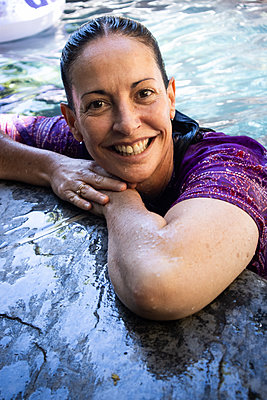 Happy woman in purple dress at the poolside - p1640m2242164 by Holly & John