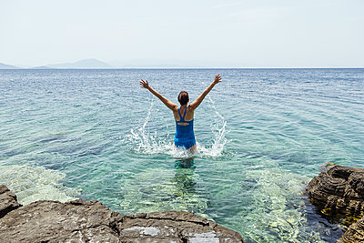Greece, Lefokastro, woman jumping into water, raised arms - p300m1581113 by Maria Maar