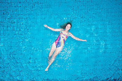 Young woman floating on water in swimming pool - p300m2103894 von Stefanie Baum