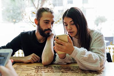 Young friends using smart phone while sitting in restaurant - p300m2242786 by Ezequiel Giménez