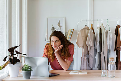 Smiling businesswoman with hand on chin using laptop at home - p300m2287115 by VITTA GALLERY