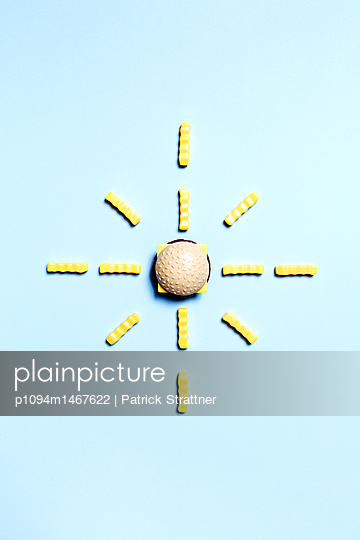 Directly above shot of burger and French fries toys arranged on blue background - p1094m1467622 by Patrick Strattner