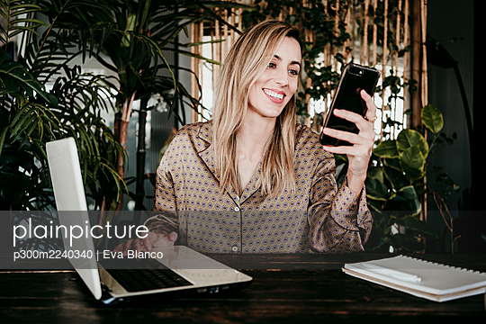 Smiling blond businesswoman using mobile phone while sitting with laptop in creative office - p300m2240340 by Eva Blanco