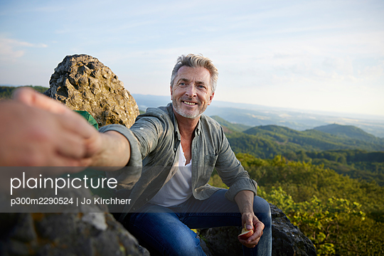 Smiling man giving apple to female friend while sitting on mountain - p300m2290524 by Jo Kirchherr
