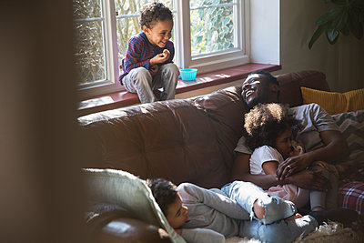 Happy father and children cuddling on living room sofa - p1023m2016582 by Sam Edwards