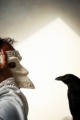 Masked man having a conversation with a dead crow - p1047m1066110 by Sally Mundy