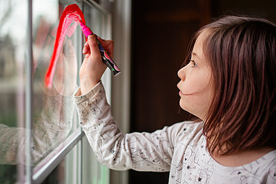 A small serious child draws a rainbow on a window with red marker - p1166m2190530 by Cavan Images