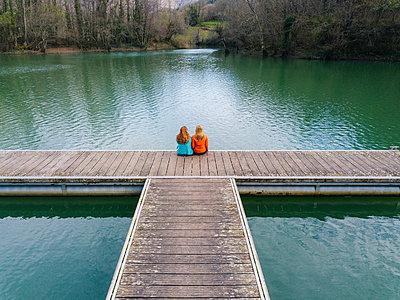 Back view of two friends sitting side by side on jetty, Valdemurio Reservoir, Asturias, Spain - p300m2180487 by Daniel González