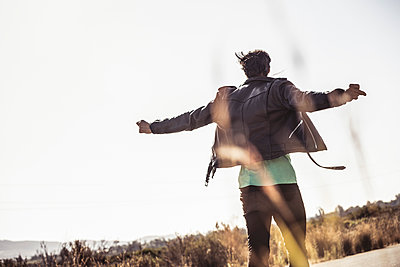 Rear view of man with outstretched arms on country road - p300m2180626 by Floco Images