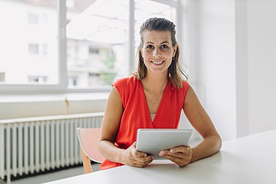 Portrait of businesswoman with digital tablet sitting in office - p300m2242735 by Gustafsson