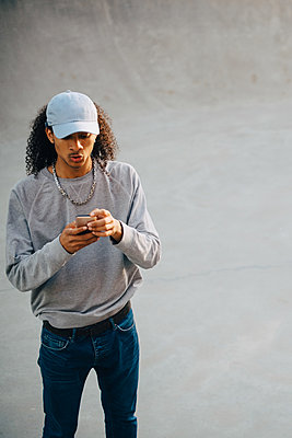 High angle view of young man using mobile phone at skateboard park - p426m2072336 by Maskot