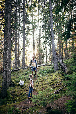 Side view of daughter looking at father in forest - p426m2212181 by Maskot