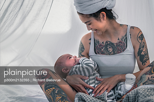 Happy tattooed young woman with her baby in canopy bed - p300m2132393 by Richárd Bellevue
