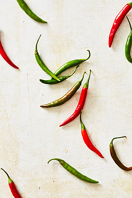 Overhead view of chili peppers on white table - p1166m2024924 by Cavan Social