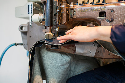 Cropped image of fashion designer sewing in jeans factory - p1185m994337f by Astrakan