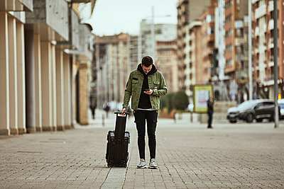 Young man with suitcase looking at mobile phone while standing on footpath in city - p300m2250055 by Aitor Carrera Porté