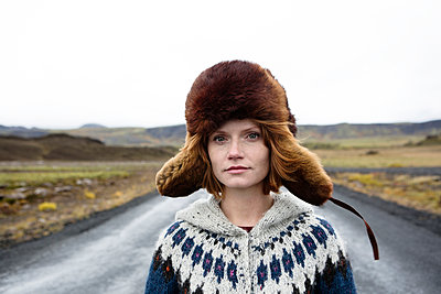 Caucasian woman wearing sweater and fur hat in middle of road - p555m1231922 by Kyle Monk
