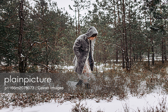 A woman walks through the woods in winter - p1166m2078073 by Cavan Images