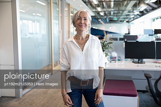 Portrait of cheerful senior businesswoman looking at camera and smiling - p1192m2123353 by Hero Images