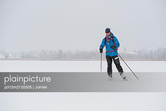 Man ice-skating on frozen lake - p312m2120505 by Johner