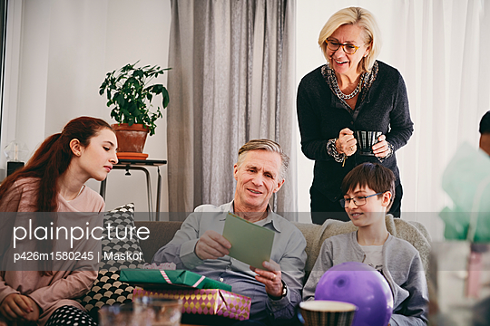 Grandfather with birthday presents reading greeting card to family in living room - p426m1580245 by Maskot