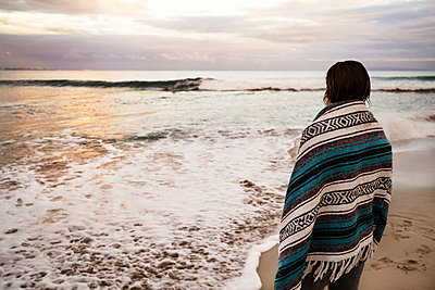 Rear view of woman wrapped in blanket standing on beach - p1166m1150455 by Cavan Images
