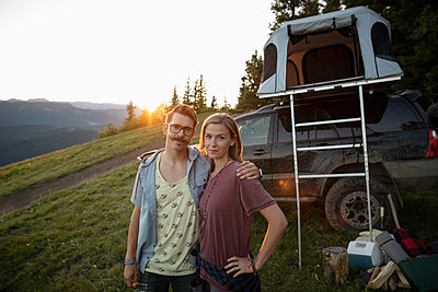Portrait couple camping, standing by SUV with rooftop tent, Alberta, Canada - p1192m2016553 by Hero Images