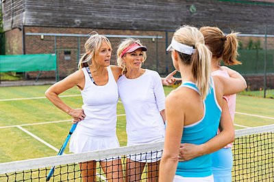 Mature women talking on grass court at tennis club - p300m2132606 by William Perugini