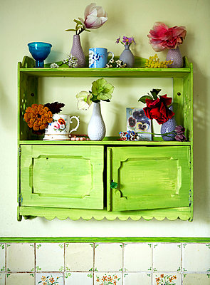 Single stem vases on green painted wall unit in Isle of Wight home;  UK - p349m920096 by Rachel Whiting
