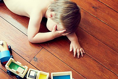High angle view of boy lying on wooden floor by toy train, head in hand - p924m1052054f by Emma Kim