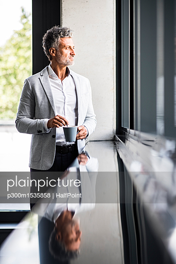 Smiling mature businessman with coffee mug looking out of window - p300m1535858 by HalfPoint