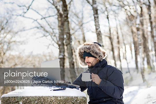 Businessman having coffee while working on laptop in snow - p300m2243625 by Jose Carlos Ichiro