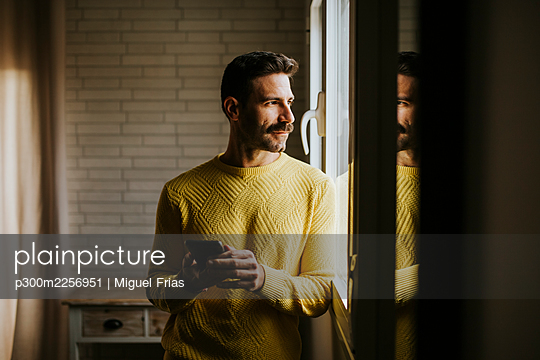 Contemplating man looking through window while holding mobile phone at home - p300m2256951 by Miguel Frias
