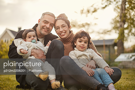 Smiling couple with children looking at camera - p312m2208201 by Plattform