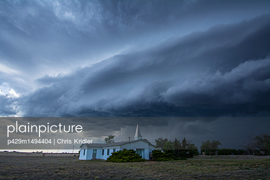 Supercell thunderstorm looms behind country church, Tatum, New Mexico, USA