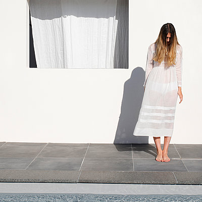 Young woman in summer dress stands at the poolside - p1105m2200690 by Virginie Plauchut