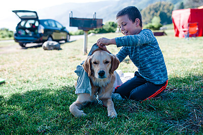 Boy playing with dog on grassy field - p1166m2112343 by Cavan Images