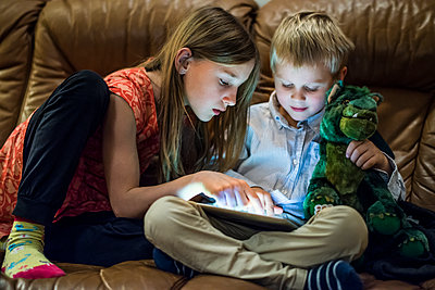 Brother and sister using digital tablet - p312m1407608 by Fredrik Schlyter