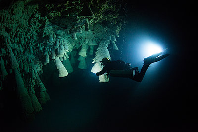 Scuba diver exploring unique natural formations known as bells in submerged caves beneath the jungle - p429m1418496 by Rodrigo Friscione