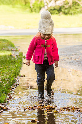 Caucasian girl wearing boots splashing in puddle - p555m1482038 by Adam Hester