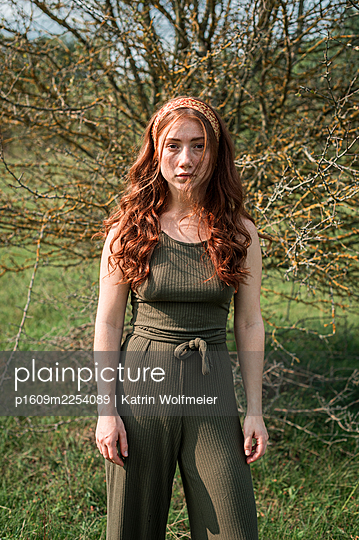 Red-haired girl in front of a bush - p1609m2254089 by Katrin Wolfmeier