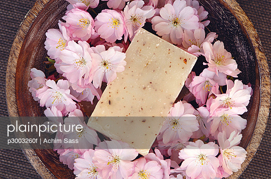 Cherry blossoms in a bowl and a bar of flavour soap, close-up - p3003260f by Achim Sass
