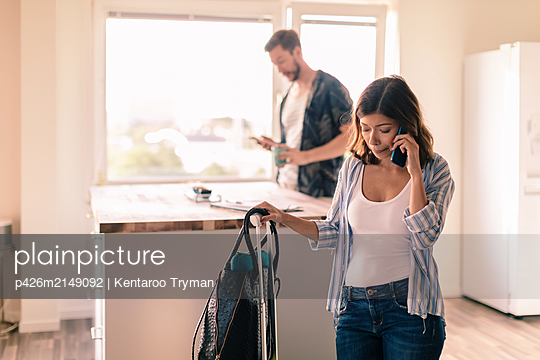 Woman with luggage talking on smart phone while man standing in background at apartment - p426m2149092 by Kentaroo Tryman
