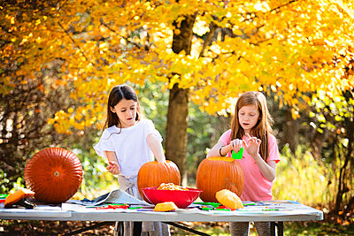 Two Young Girls Carving Pumpkins Outdoors - p1166m2147192 by Cavan Images