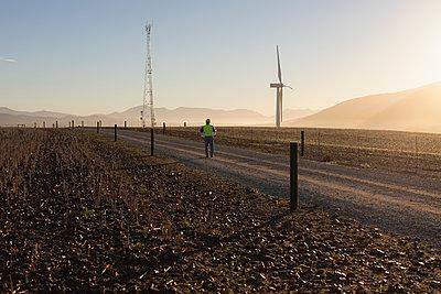 Rear view of engineer walking at a wind farm - p1315m2002989 by Wavebreak