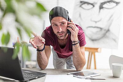 Artist on cell phone in studio - p300m2013309 von zerocreatives