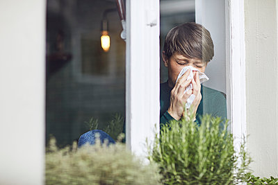 Woman blowing her nose at home at the window - p300m2188888 by Maya Claussen